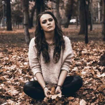 На фото дівчина сидить на жовтому литті, сумна