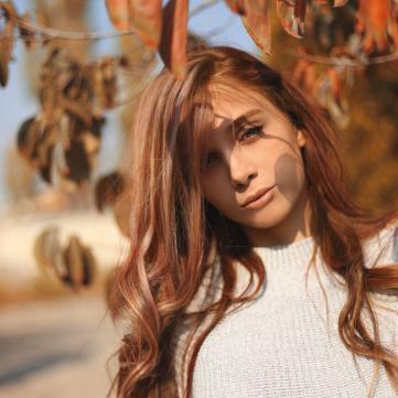Фото дівчини серед осіннього листя.