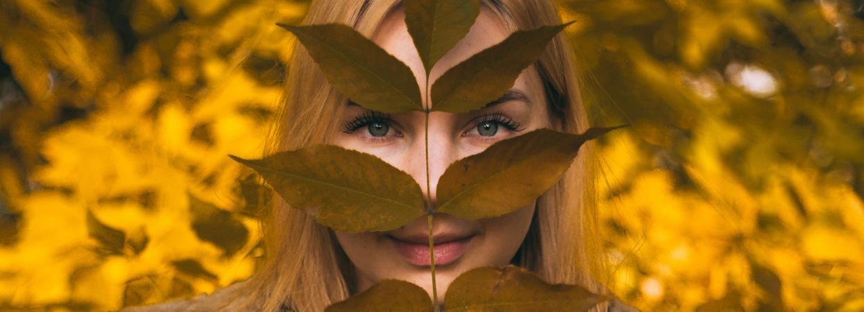 Дівчина тримає гілку з осіннім листям.
