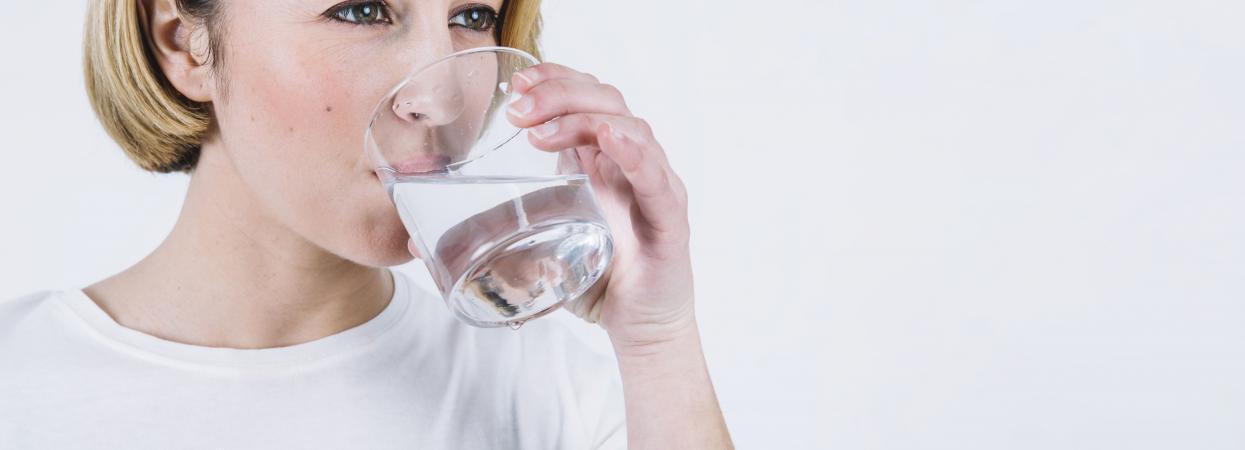 На фото жінка п'є воду