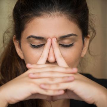 сумна жінка із заплющеними очима думає