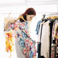 на фото жінка обирає собі сукню в магазині