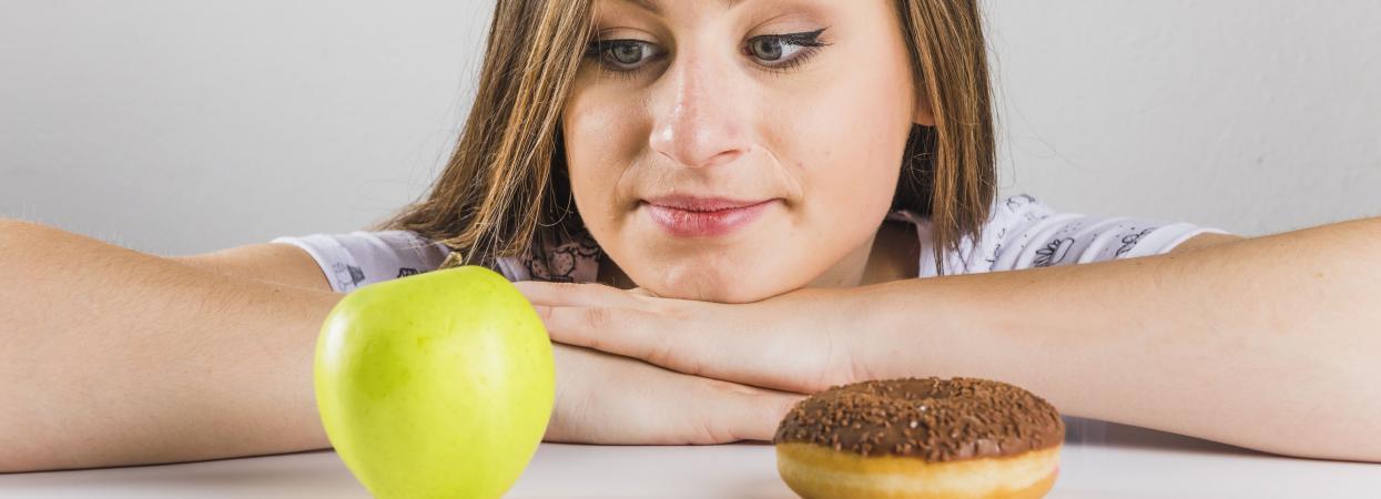 на фото дівчина, яблуко і пончик