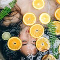 на фото дівчина у ванні з лимонами