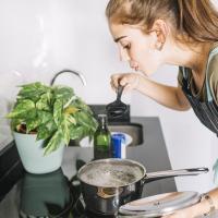 Жінка на кухні куштує суп