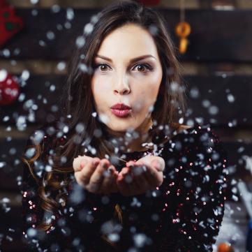 на фото дівчина здуває сніг з долонь