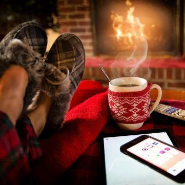 на фото ноги, чашка чаю і камін