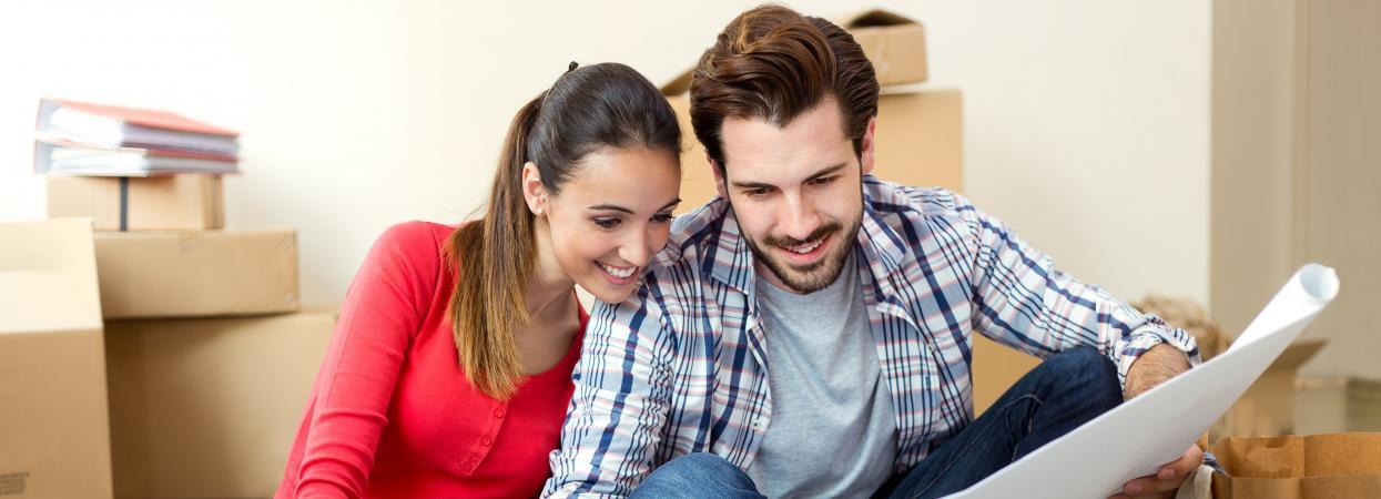 на фото муж и жена смотрят на карту
