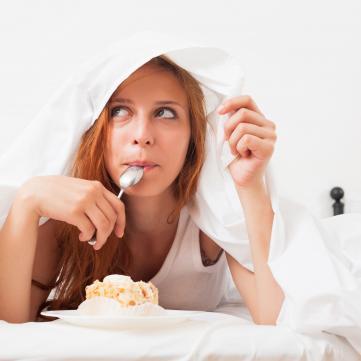 на фото Жінка Їсть під ковдрою