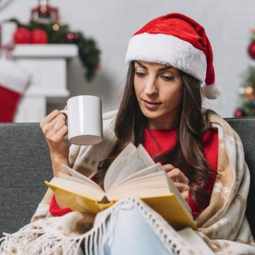 Дівчина у шапочці санти читає книжку і п'є каву