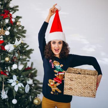 на фото дівчина біля ялинки тримає коробку з подарунком