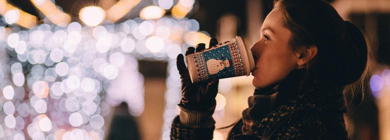 Девушка пьет теплый напиток зимой.