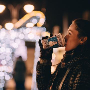 Дівчина п'є теплий напій взимку