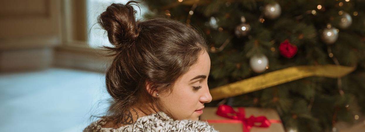 Дівчина сумує біля ялинки, післясвяткова депресія