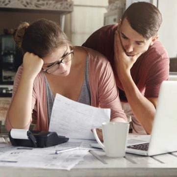 на фото чоловік та жінка вивчають  рахунки