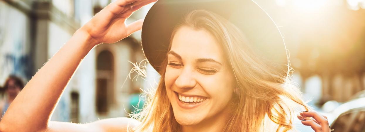 Девушка в шляпе смеется
