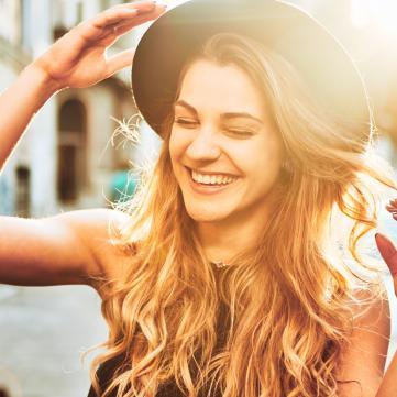Дівчина в капелюшку сміється