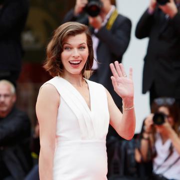 акторка мілла йовович  у білій сукні на червоній доріжці