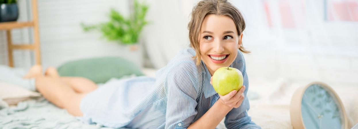 дівчина їсть яблуко