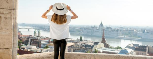 Дівчина у білому капелюшку дивиться на парламет у Будапешті