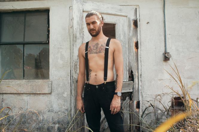 Красивий чоловік з голим торсом і в штанах з підтяжками