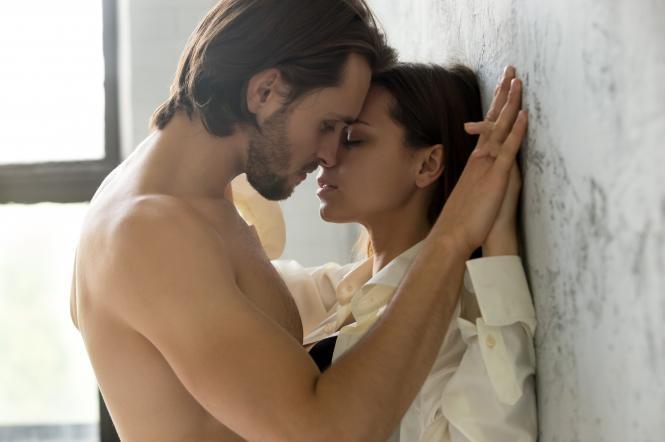 Пара целуется возле стены